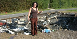 Irish Traveller in front of a trailer destroyed in an arson attack