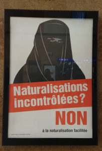 SVP poster being put up in train stations in Switzerland (Credit: Graham Murray)