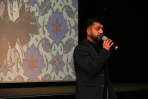 Riz giving speech at event