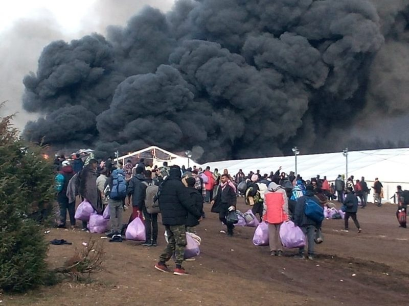 Image of the breaking out in the Lipa camp. Large plumes of smoke in the background and people carrying bags with their belonging in the foreground.