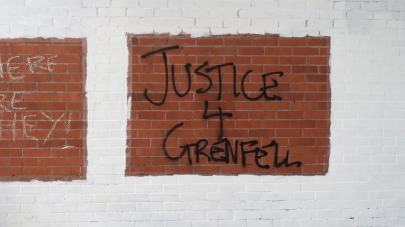 Justice for Grenfell graffiti on a brick wall.