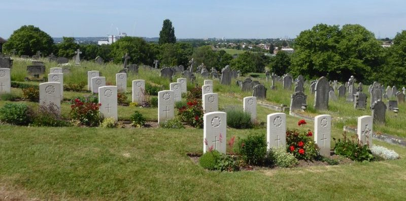 Commonwealth War Graves in Greenwich Cemetery, London, on a sunny day.